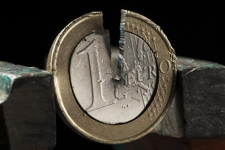 A damaged one Euro coin being held in a vise is pictured in this photo illustration taken in Warsaw September 11, 2012. REUTERS/Kacper Pempel