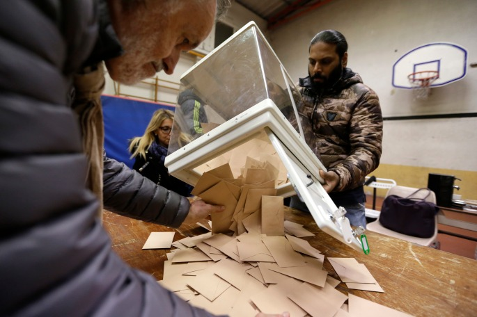 Volunteers empty a ballot box after the conservatives primary runoff at a polling station Sunday, Nov. 27, 2016 in Marseille, southern France. French conservatives voted for their nominee in next year's presidential election, choosing between two former prime ministers with some similar ideas on the economy but divergent views on how to prevent further terror attacks on French soil. (AP Photo/Claude Paris)