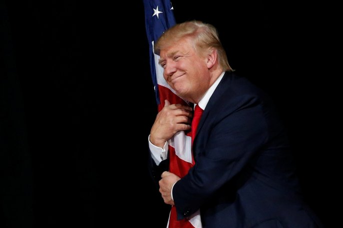 trump-hugs-a-us-flag-as-he-comes-onstage-to-another-rally-with-supporters-in-tampa-florida-on-october-24